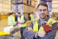 Worker holding tape dispenser in warehouse - CAIF02865