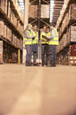 Workers talking in warehouse - CAIF02868