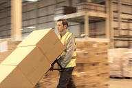 Worker carting boxes in warehouse - CAIF02874