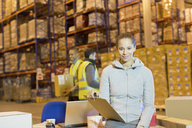 Worker holding clipboard in warehouse - CAIF02877