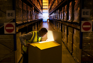Worker opening glowing box in warehouse - CAIF02880