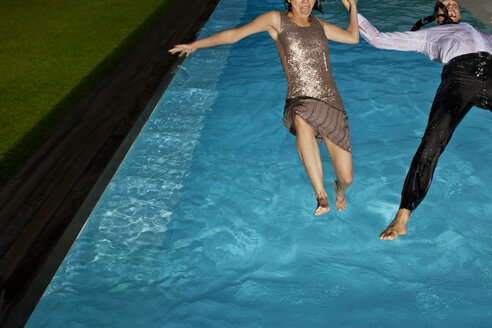 Fully dressed couple jumping into swimming pool - CAIF02886