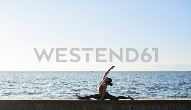 Young woman practicing yoga on a wall by the sea - IGGF00441