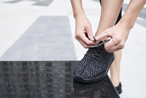 Woman tying her shoe before workout - IGGF00459
