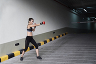 Female boxer boxing in a garage - IGGF00466