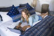 Smiling woman lying in bed using laptop - SBOF01417