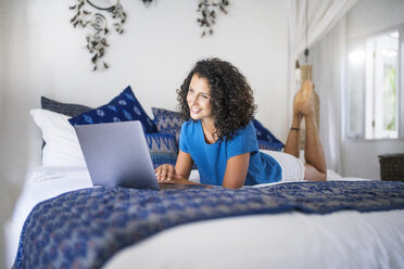 Smiling woman lying in bed using laptop - SBOF01420