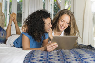 Two happy women lying in bed using tablet - SBOF01426