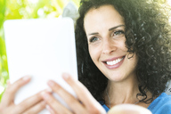 Portrait of smiling woman holding e-reader - SBOF01429