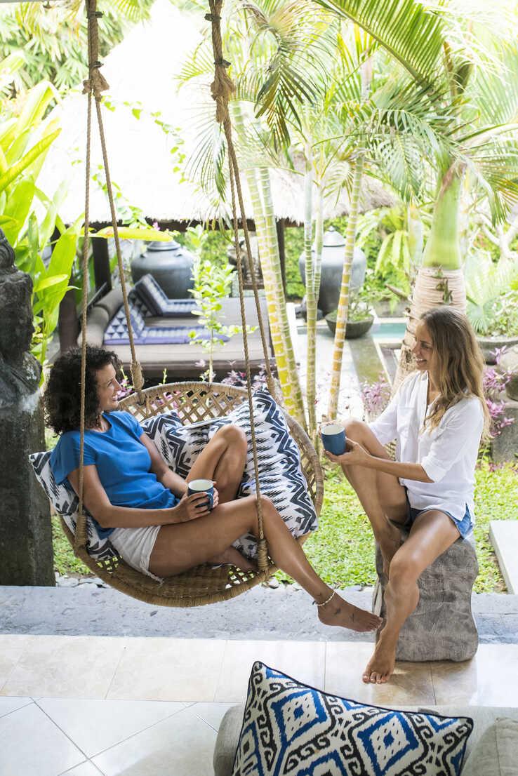 Two smiling women talking on terrace having a cup of coffee - SBOF01432 - Steve Brookland/Westend61