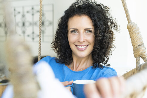 Portrait of smiling woman with curly hair holding cup of coffee - SBOF01435