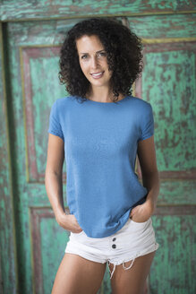Portrait of smiling woman with curly hair - SBOF01441