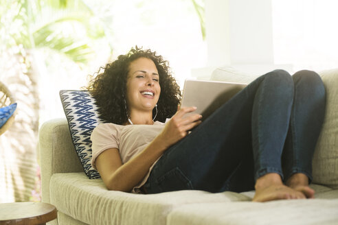 Happy woman lying on sofa with earphones and tablet - SBOF01447