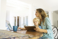 Boy sitting on his mother's lap and looking at a tablet while his mother is working on a laptop - SBOF01459