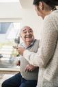 Senior man smiling at nurse with stethoscope at home - UUF12869