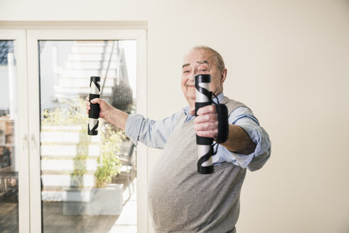 Portrait of smiling senior man doing an arm exercise - UUF12878