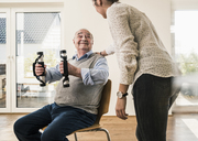 Young woman supporting senior man doing an arm exercise - UUF12881