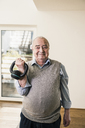 Portrait of smiling senior man doing a weight exercise - UUF12884