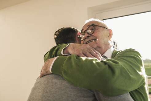 Smiling senior man hugging young man - UUF12890