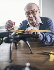 Portrait of senior man working on a drone - UUF12899