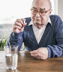 Portrait of senior man sitting at table with pill and glass of water - UUF12902