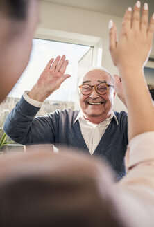 Happy senior man with raised hands looking at young woman - UUF12914