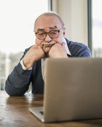 Senior man sitting at table looking at laptop - UUF12920