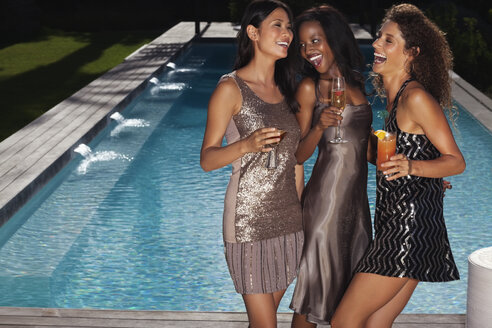 Women having drinks by swimming pool - CAIF03036