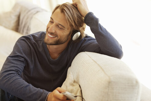 Man listening to headphones on sofa - CAIF03057