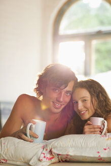 Couple having coffee together in bed - CAIF03135