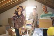 Friends unpacking boxes in attic - CAIF03144