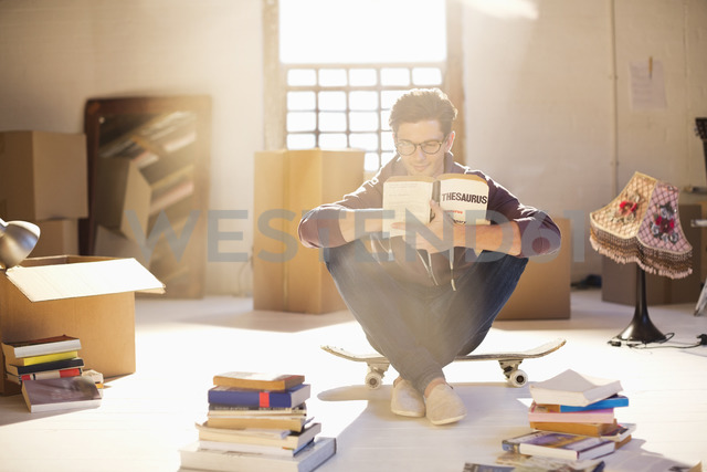 Man reading in new home - CAIF03159