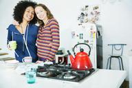Women hugging in kitchen - CAIF03177