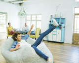 Man jumping into beanbag chair - CAIF03183