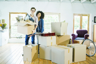 Couple unpacking boxes in new home - CAIF03207