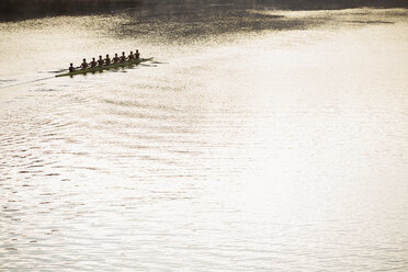 Rowing team in scull on sunny lake - CAIF03231