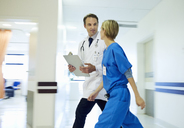 Doctor and nurse walking in hospital hallway - CAIF03252