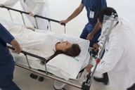 Hospital staff rushing patient to operating room - CAIF03273
