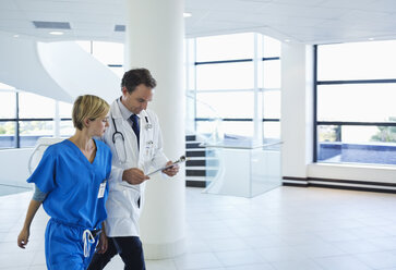 Doctor and nurse talking in hospital hallway - CAIF03285