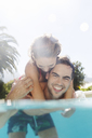 Couple playing in swimming pool - CAIF03315