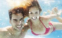 Couple swimming in pool - CAIF03321