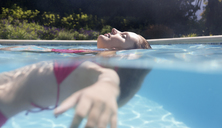 Woman floating in swimming pool - CAIF03327