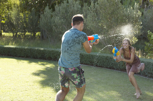 Couple playing with water guns in backyard - CAIF03354