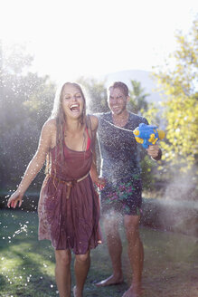 Couple playing with water guns in backyard - CAIF03366