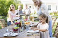 Family setting table outdoors - CAIF03387