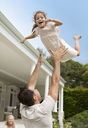 Father and daughter playing outside house - CAIF03396