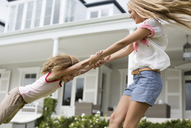 Mother and daughter playing outside house - CAIF03402