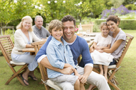 Family smiling at table outdoors - CAIF03405