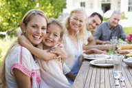 Mother and daughter hugging at table outdoors - CAIF03411