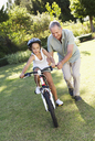 Older man teaching granddaughter to ride bicycle - CAIF03423